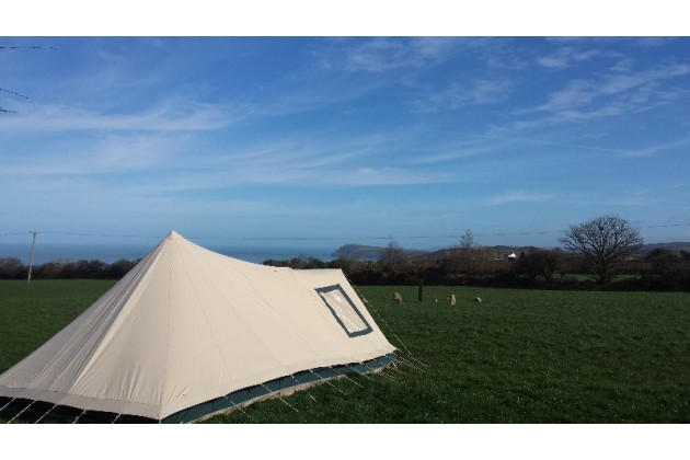 Sunny day at Glasfryn Escapes campsite in Fishguard Pembrokeshire. Pre-set up tents in a quite open field with sea views.